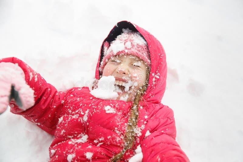 Speels meisje die met vlechten in de eerste sneeuw spelen royalty-vrije stock foto