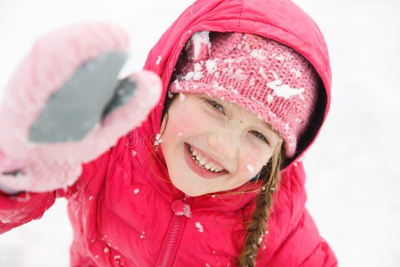 Speels meisje die met vlechten, van de winter en sneeuw genieten stock afbeelding