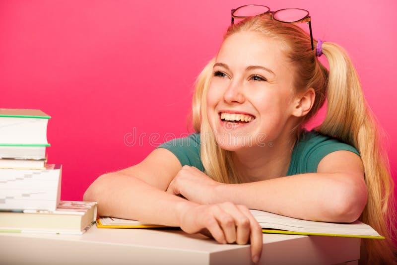 Speels schoolmeisje met twee haarstaarten en grote oogglazen leanin stock fotografie