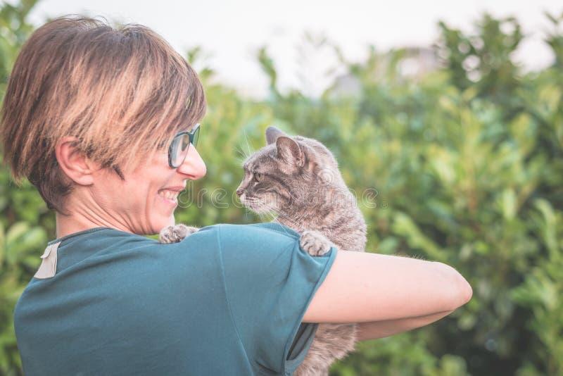 Speelse binnenlandse die kat door glimlachende vrouw met oogglazen wordt gehouden en wordt geknuffeld Het openlucht plaatsen in g royalty-vrije stock foto