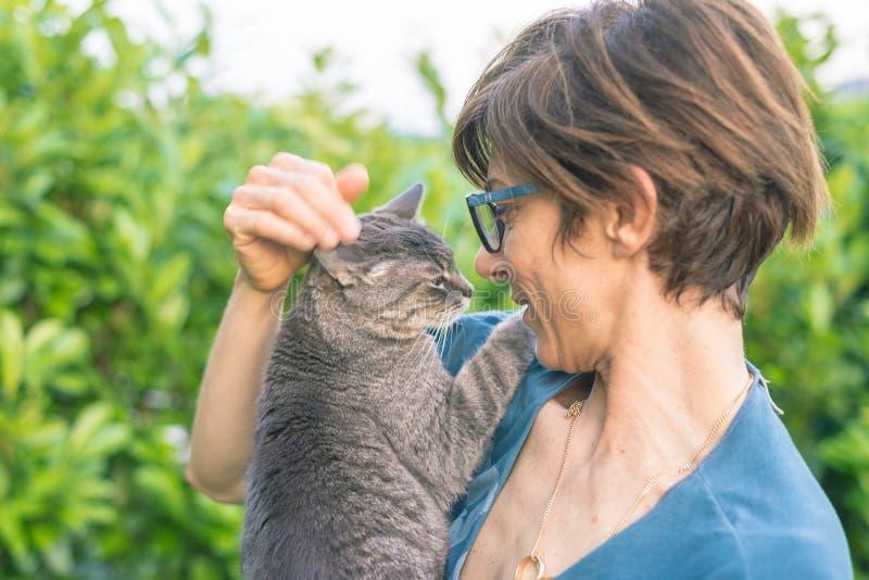 Speelse binnenlandse die kat door glimlachende vrouw met oogglazen wordt gehouden en wordt geknuffeld Het openlucht plaatsen in g royalty-vrije stock afbeeldingen