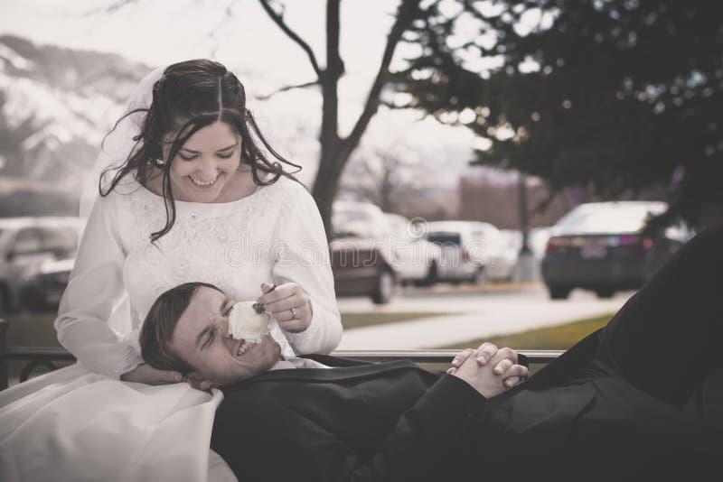 Speelse Bruid en Bruidegom Sitting op een Bank royalty-vrije stock foto