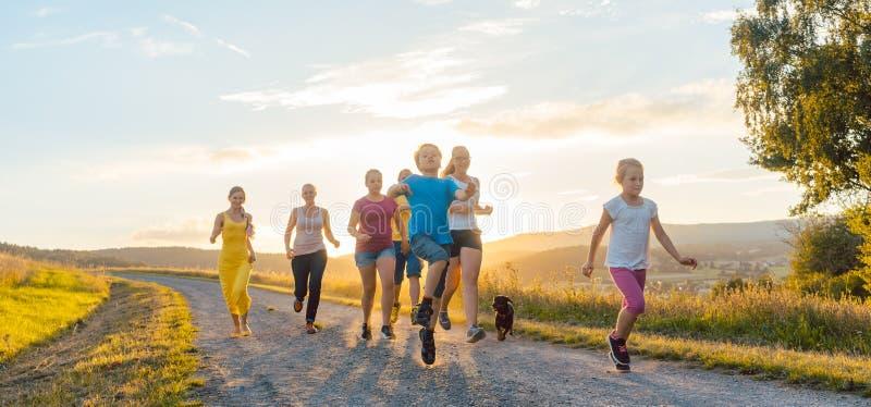 Speelse familie die en op een weg in de zomerlandschap lopen spelen stock fotografie