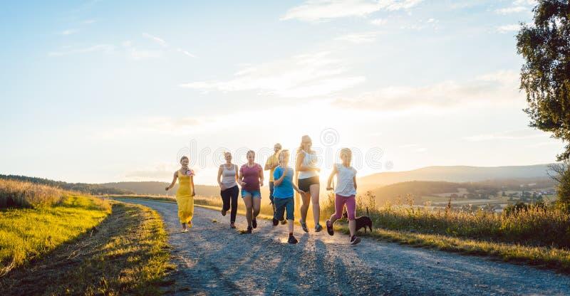 Speelse familie die en op een weg in de zomerlandschap lopen spelen stock foto's