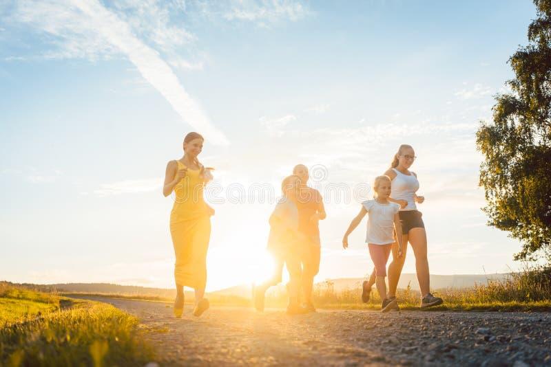 Speelse familie die en op een weg in de zomerlandschap lopen spelen royalty-vrije stock fotografie