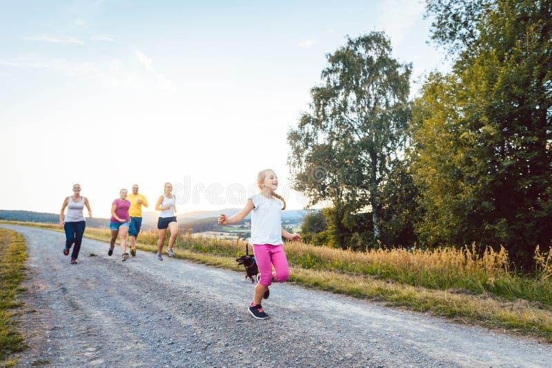 Speelse familie die en op een weg in de zomerlandschap lopen spelen royalty-vrije stock afbeeldingen