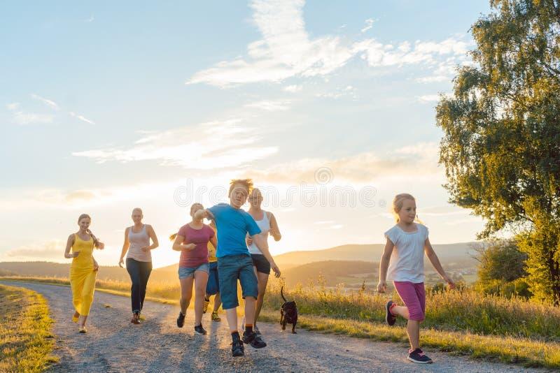 Speelse familie die en op een weg in de zomerlandschap lopen spelen stock foto