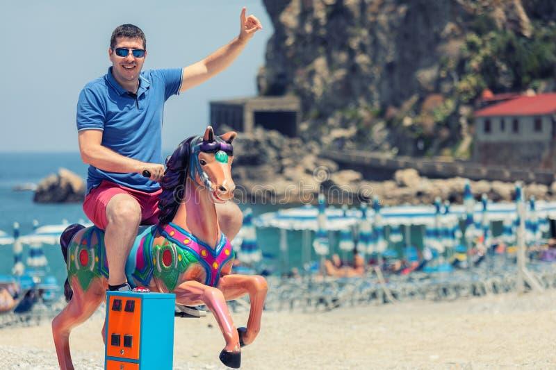 Speelse gekke mensenpapa die houten hobbelpaard berijden bij strand, Gelukkige volwassen kerel die pret op speelplaats in de zome royalty-vrije stock afbeeldingen