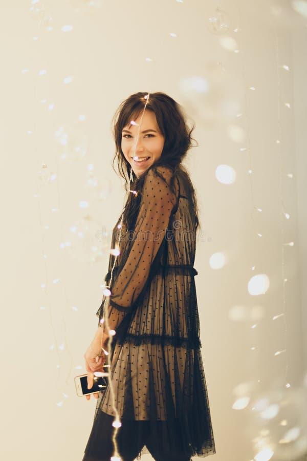 Speelse jonge vrouw in cocktailkleding die glimlachend over lichtenachtergrond blijven royalty-vrije stock foto