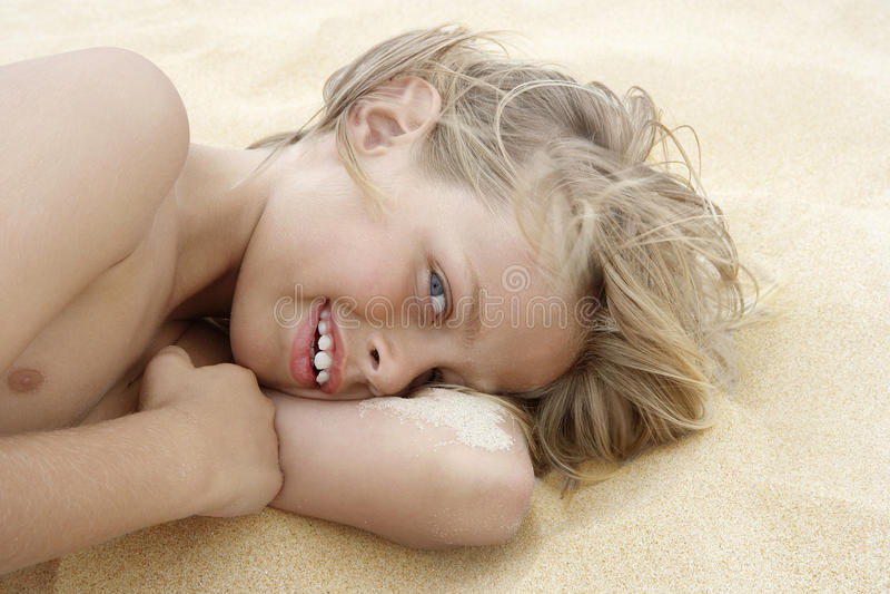 Speelse Jongen die op Zand liggen royalty-vrije stock afbeeldingen