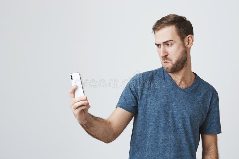 Speelse Kaukasische mens die met donker haar, blauwe ogen en baard mobiele telefoon houden, die voor selfie stellen, die gezichte stock afbeelding