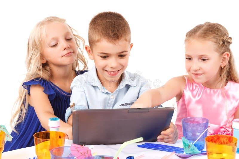 Speelse kinderen die met laptop zitten stock afbeeldingen
