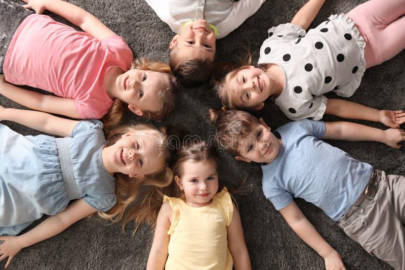 Speelse kleine kinderen die op tapijt binnen liggen stock afbeeldingen