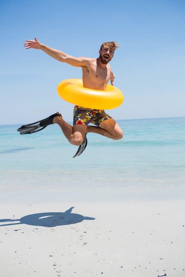 Speelse mens die opblaasbare ring dragen die op kust springen royalty-vrije stock fotografie