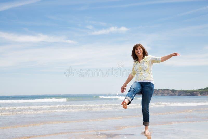 Speelse midden oude vrouw op het strand royalty-vrije stock afbeelding
