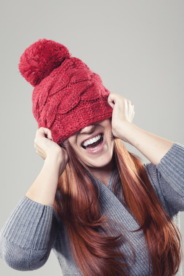 Speelse mooie vrouw die de rode winter dragen beanie royalty-vrije stock foto