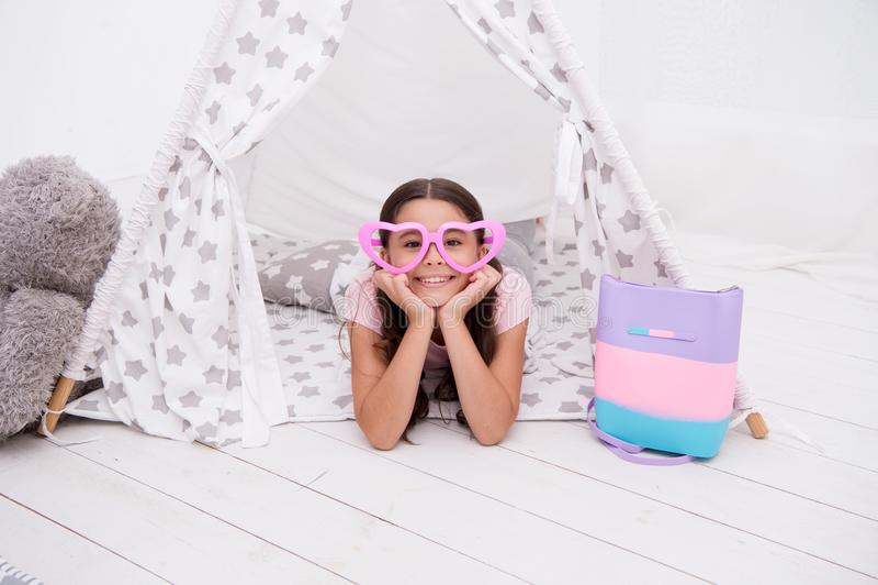 Speelse stemming Vormde het meisjes leuke kind in hart oogglazen legt het ontspannen in tipi in haar slaapkamer Leuke ruimte voor stock afbeelding