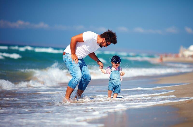 Speelse vader en peuterzoon die pret hebben die in overzeese golven tijdens de zomervakantie springen, de activiteitenspelen van  stock foto's