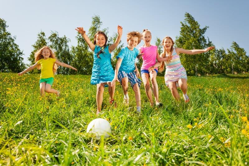 Speelse vrienden die aan de bal op gebied lopen stock foto