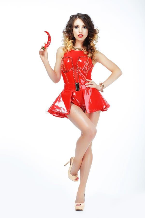 Speelse Vrouw in Rode Latexkleding met Heet Chili Pepper stock afbeelding