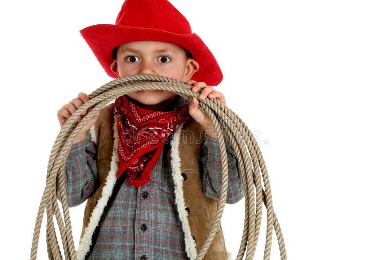 Speelse zeer jonge cowboy die rode hoed dragen en een kabel houden stock afbeeldingen