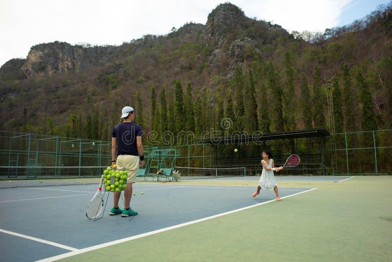 Speelt het portret Aziatische meisje tennis met haar vader en bus bij openluchthof met steenberg en bosachtergrond stock foto's