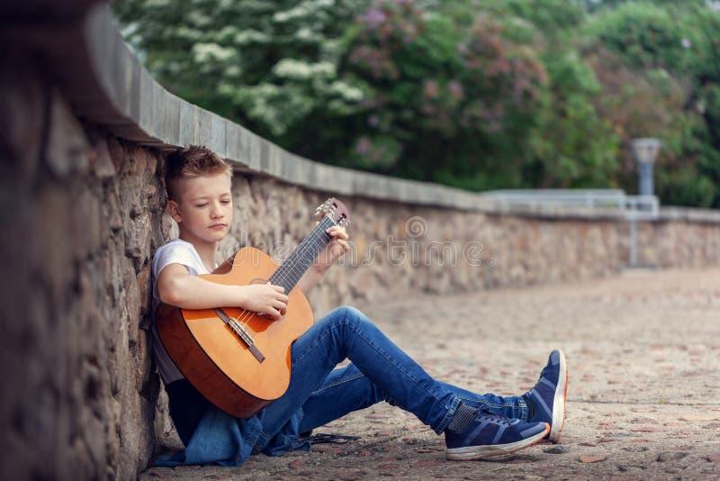 Speelzitting van de tiener de akoestische gitaar op de stappen in het park stock foto's