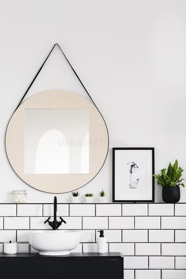 Spegel bredvid affischen och växten i vit- och svartbadruminre med handfatet Verkligt foto arkivfoton