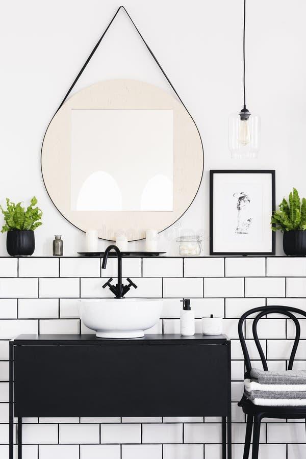 Spegel mellan växten och affischen i vit- och svartbadruminre med stol Verkligt foto fotografering för bildbyråer