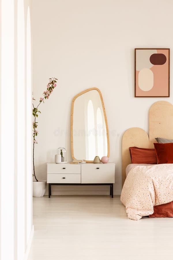 Spegel på det vita kabinettet bredvid säng med huvudgaveln under affischen arkivfoto
