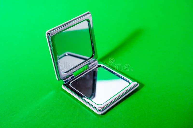 Spegel på grön bakgrund arkivfoto
