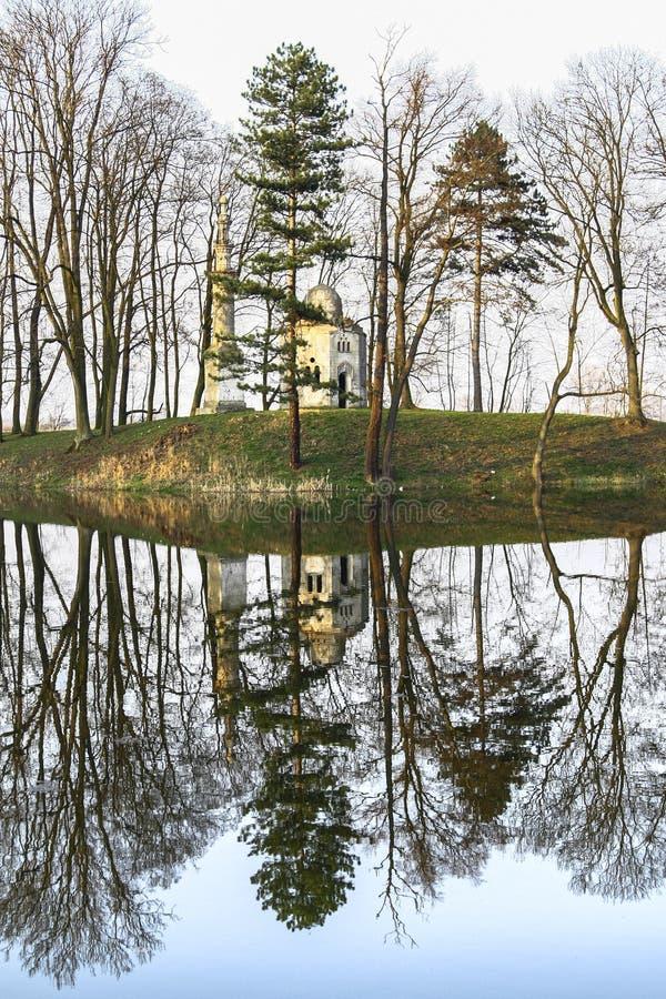 Spegelförsett landskap med en gammal gazebo bland träden arkivbild