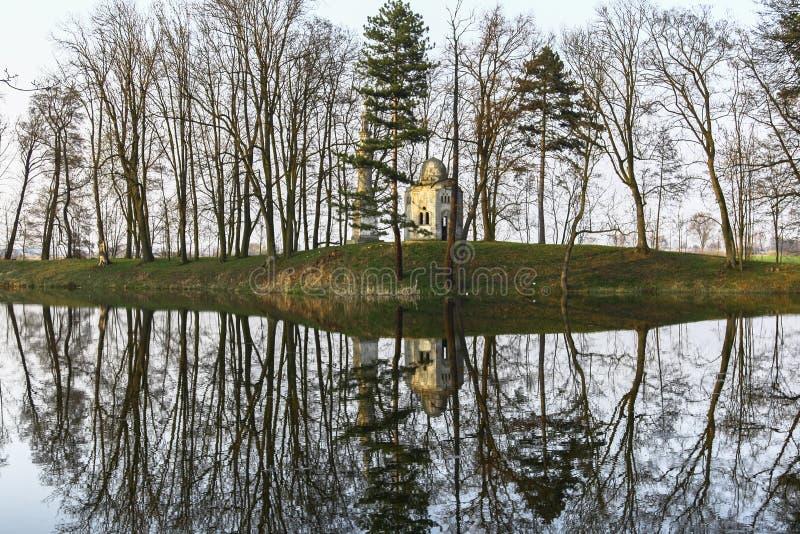 Spegelförsett landskap med en gammal gazebo bland träden royaltyfri bild