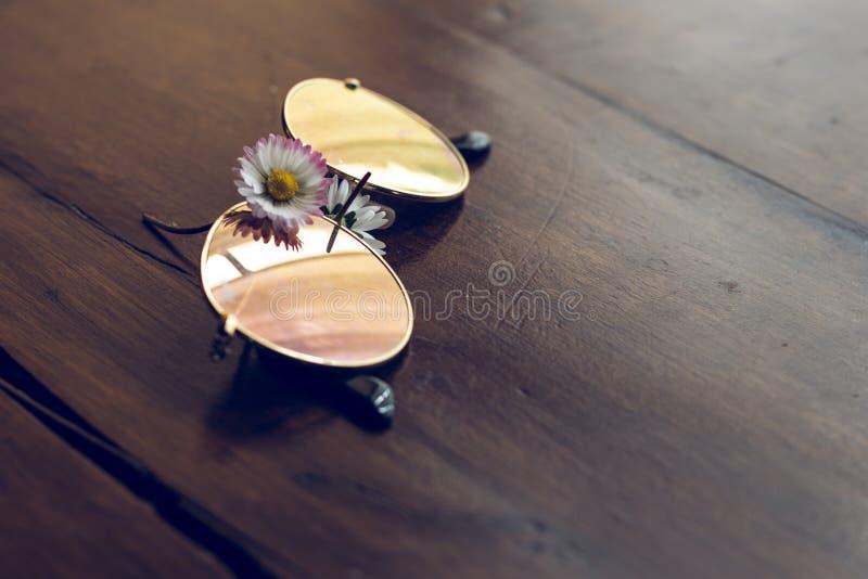 Spegelkvinnasolglasögon med en tusenskönablomma på en träbrädetabell arkivfoto