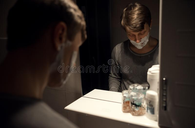 Spegeln av mannen som rakar i badrum fotografering för bildbyråer