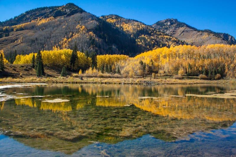 Spegeln som reflexion i en klar sjö, reflekterande berg med höst färgar arkivbilder