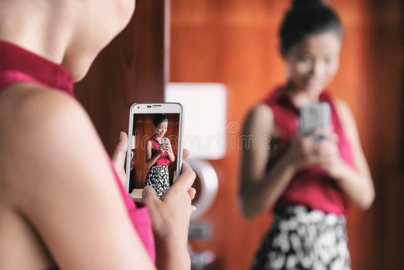 Spegelselfiekvinna som tar bilden med mobiltelefonen i lagerspegelshopping för kläder som ser hennes modeoufit för kontor royaltyfria foton