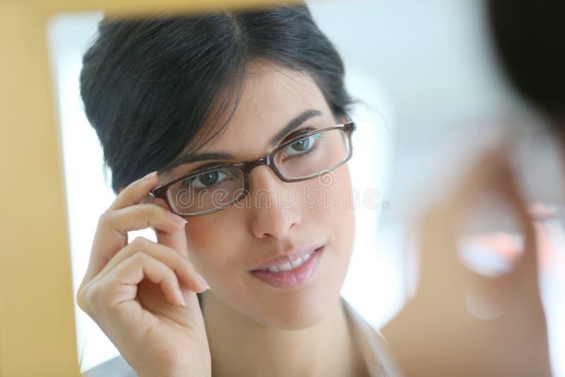Spegelstående av bärande glasögon för kvinna arkivbild