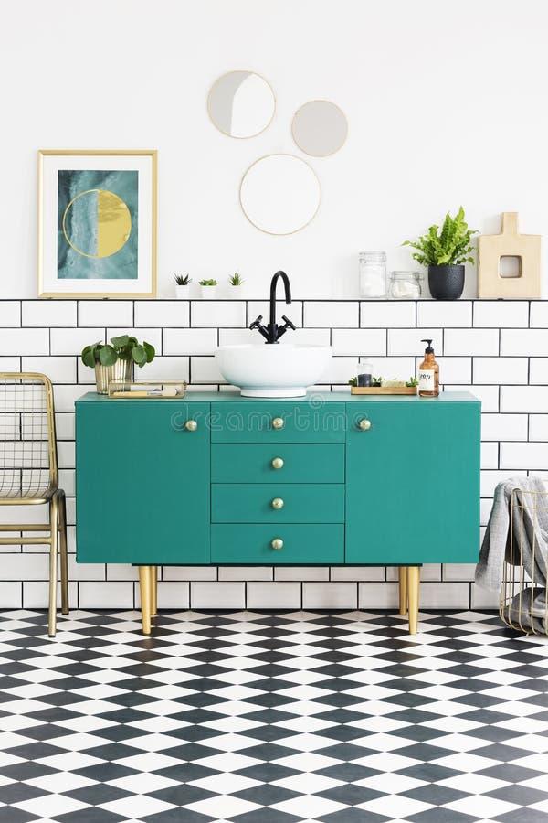 Speglar och ovannämnt grönt kabinett för affisch i badruminre med guld- stol och växter Verkligt foto royaltyfri fotografi