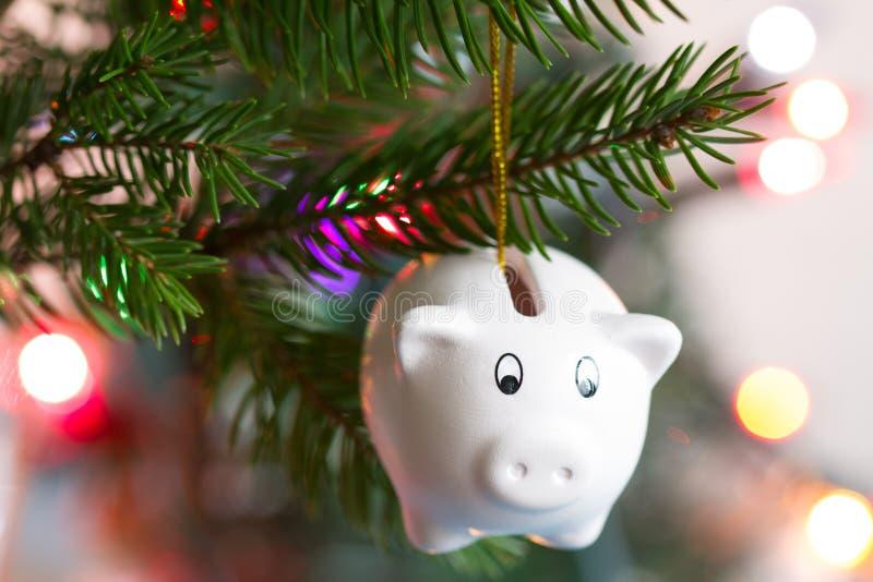 Speichern Sie Geld- und Weihnachtskonzept mit Sparschwein und Baum stockbild