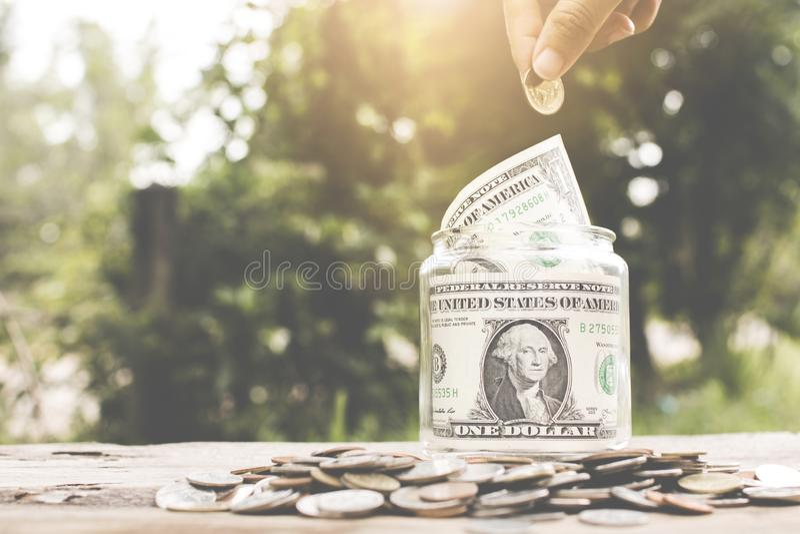 Speichern Sie Geldkonzept, die Hand, die Geldmünze in Glasgefäß einsetzt stockbilder