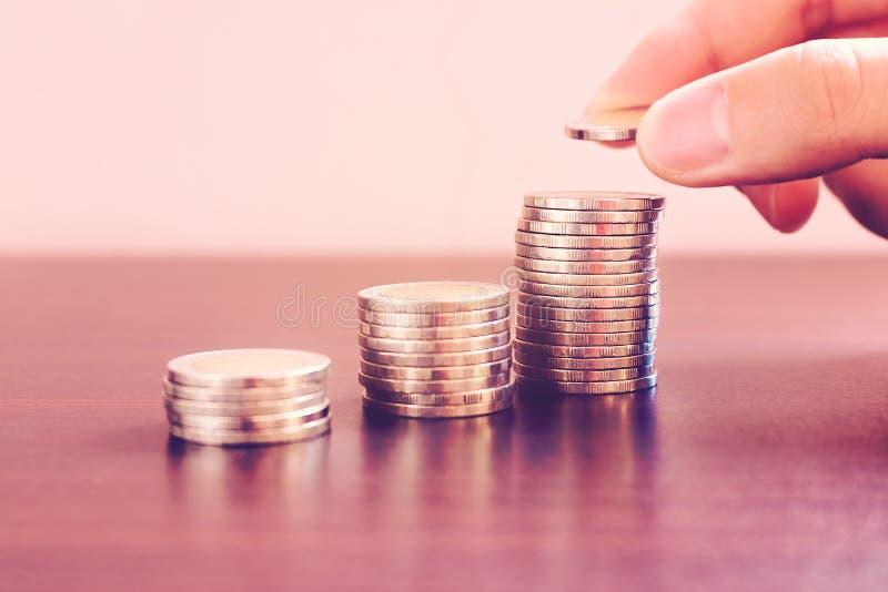 Speichern Sie Geldkonzept mit dem Handmann, der Münze auf Stapelsatz setzt stockfotografie