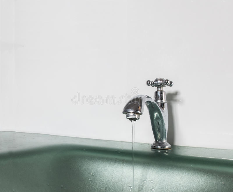 Speichern Sie Wasser-Abwehr das Weltkonzept, Wasser-Tropfen vom alten silbernen Hahn des Badezimmers mit Copyspace lizenzfreies stockfoto