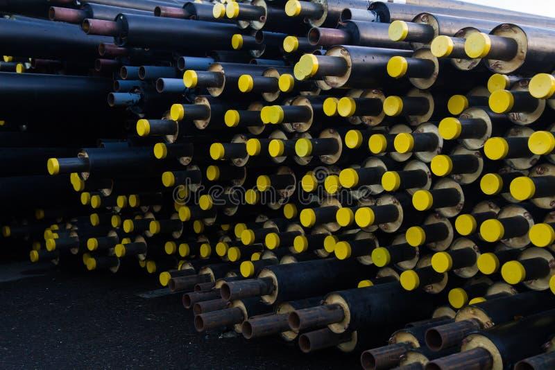Speicherte viel schwarzes Stahlrohr mit Wärmedämmung auf Baustelle in einer Kunststoffrohrverpackung, die mit gelben Deckelrohren lizenzfreie stockfotografie