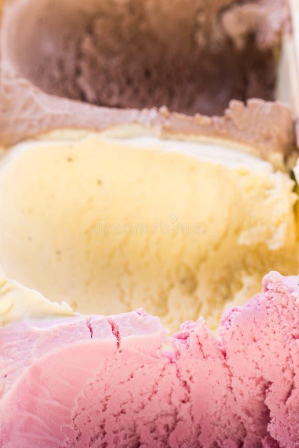 Speiseeiscremeerdbeere, Vanille und Schokolade - einige Schaufeln bereits genommen aus dem Eiscremekasten heraus stockbild