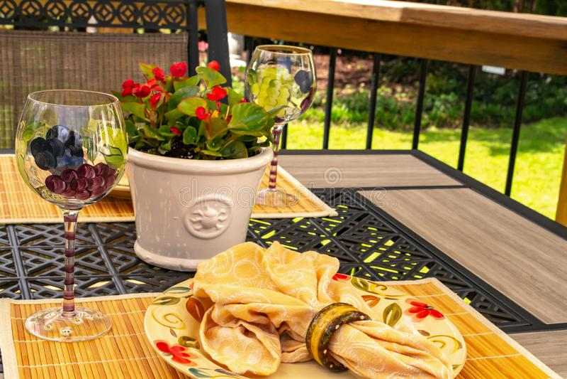 Speisen-gelbe Platte des Patios und Hand [gemaltes Weinglas, Unterhaltung im Freien lizenzfreie stockfotografie