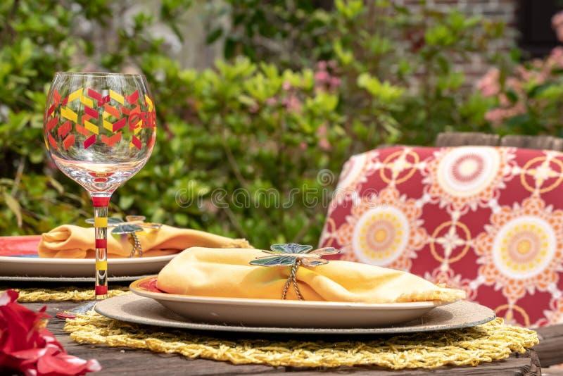 Speisen-gelbe Platte des Patios und handgemaltes Weinglas, Unterhaltung im Freien stockbild