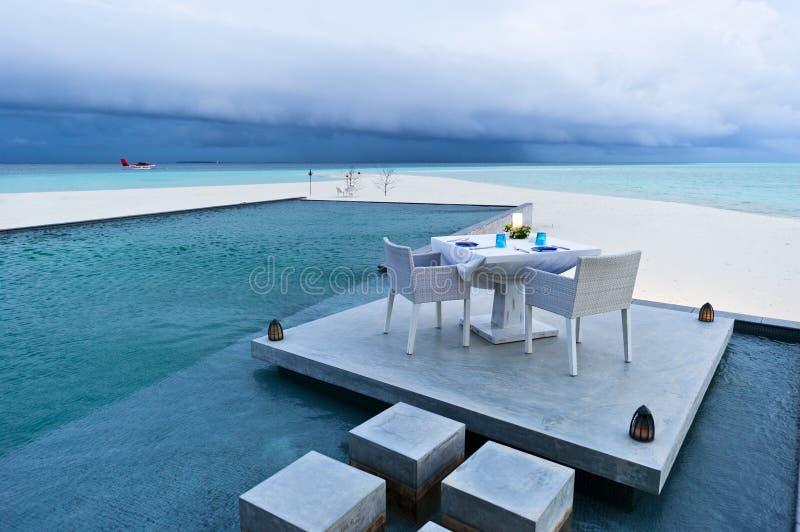 Speisetisch auf der Plattform des Swimmingpools stockfotos