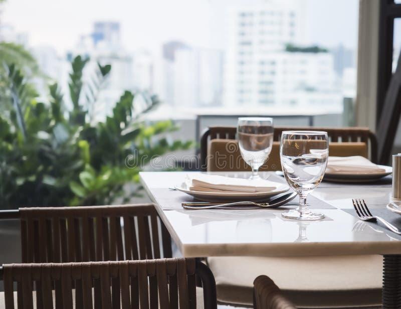 Speisetisch-gesetzter Restaurantinnenraum mit Garten und Skylinen VI stockfotos