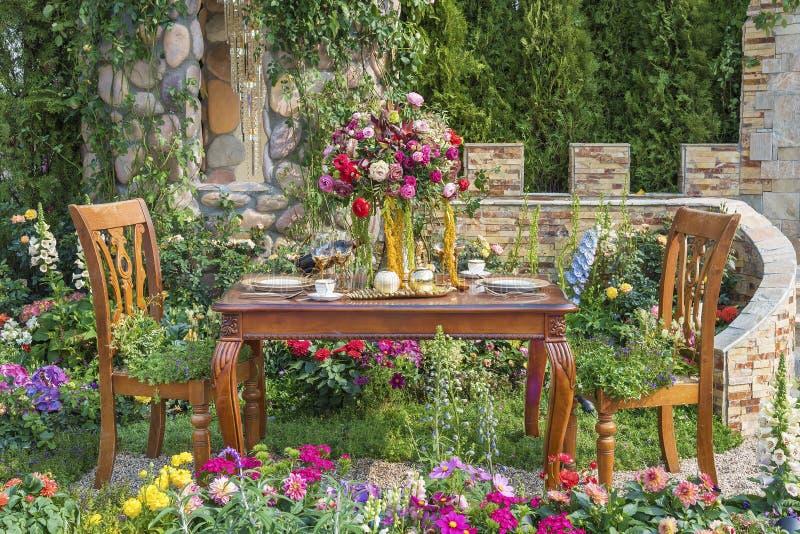 Speisetisch im Blumengarten lizenzfreie stockfotografie